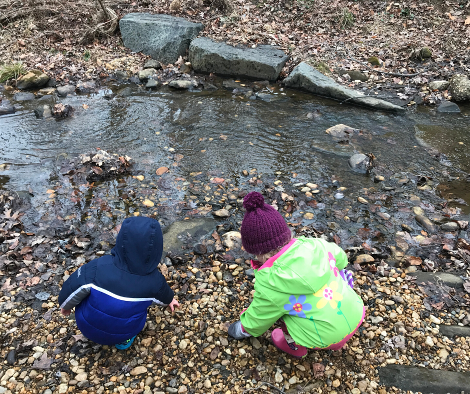 Kids wearing winter gear playing near a stream